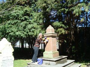 Joan Worthington cleans the Percy Grave